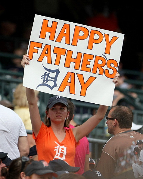 "A fan holds up a ""Father's Day"" sign"