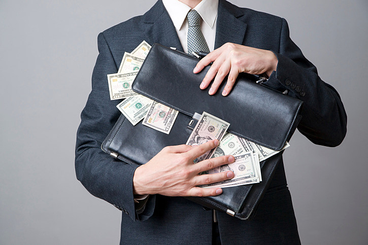 Businessman with a briefcase full of money in the hands